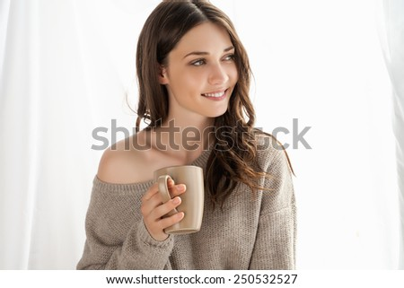 Closeup of beautiful girl with cup enjoying the freshness of the new day and looking through the window.  - stock photo