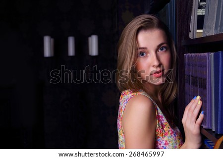 Closeup of beautiful girl with long blond hair near shelf of books looking at camera - stock photo