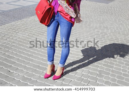 Closeup of beautiful legs in high heels shoes of a woman walking in sunny city streets. Pretty woman in jeans and bright pink shoes. Street fashion look. - stock photo