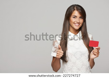 Closeup of beautiful smiling business woman showing red card in hand and gesturing thumb up, over gray background - stock photo