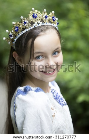 Closeup of beautiful smiling princess girl with long brunette hair in traditional ukrainian embroidery white blue colors and beautiful diadem with diamonds in gold outdoor, vertical picture - stock photo