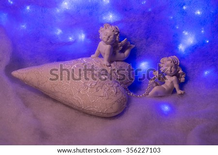 Closeup of beautiful soulful figurine composition of cupid angels for valentine day or christmas with small pillow in shape of heart lying on white wadding decorating snow with bright light sparks - stock photo