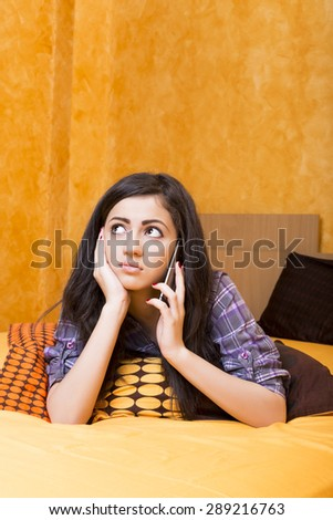 Closeup of  beautiful teenage girl speaking on  smart phone on the bed in her bedroom - stock photo
