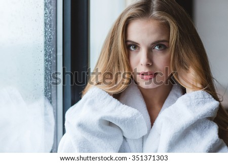 Closeup of beautiful thoughtful young woman with long blonde hair in bathrobe standing near the window - stock photo