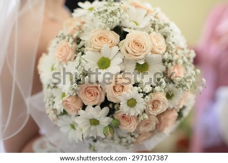 Closeup of beautiful wedding bunch of rose and chrysanthemum flowers pink orange, white colours with bride on blur background, horizontal picture - stock photo