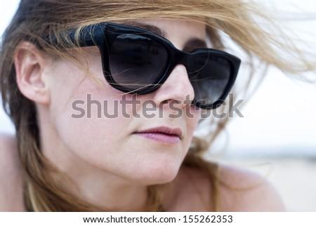 Closeup of beautiful woman in sunglasses on a beach - stock photo