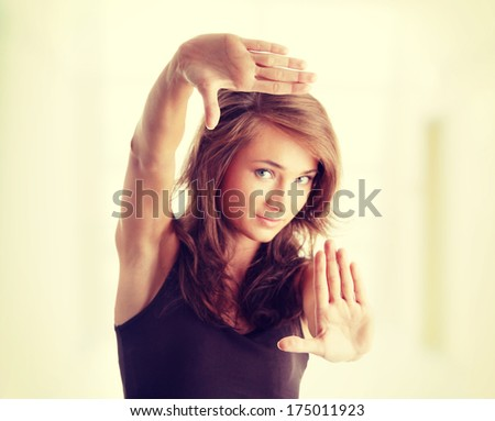 Closeup of beautiful woman making frame with her hands - stock photo