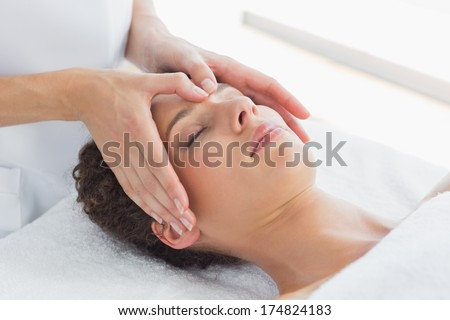 Closeup of beautiful woman receiving massage on forehead in health spa - stock photo