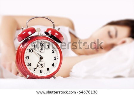 Closeup of beautiful woman sleeping and alarm clock (focus on alarm clock). - stock photo