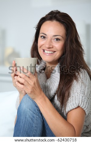 Closeup of beautiful woman with hot drink at home - stock photo