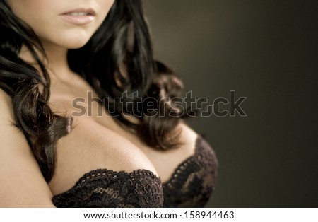 Closeup of beautiful womans' breasts, black lacy brassiere, very shallow depth of focus - stock photo