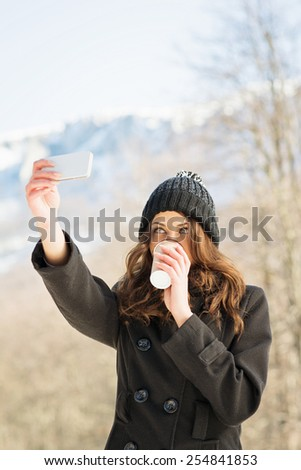 Closeup of beautiful young Caucasian woman in black coat and knit beanie hat drinking coffee taking a selfie with smartphone outdoors in winter. Vertical, copy space, mild retouch, natural light. - stock photo