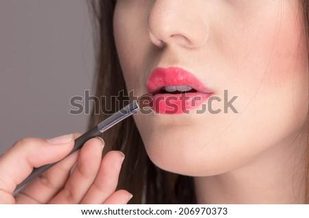 closeup of beautiful young woman applying pink red lipstick - stock photo