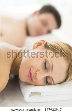 Closeup of beautiful young woman resting on massage table with man in background at spa - stock photo
