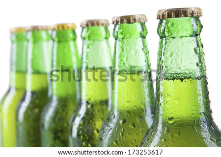 Closeup of beer bottles with condensation. Isolated on white. - stock photo