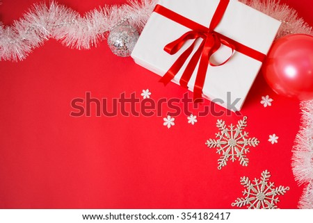 Closeup of big white Christmas gift box with red ribbon on red background with other decorations around it. Horizontal, vibrant color, no filter, copy space, shot from above. - stock photo
