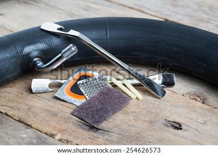 Closeup of bike tire repair kit on wooden table - stock photo