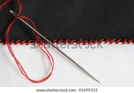 Closeup of black and white textile material jointed by red thread seam - stock photo
