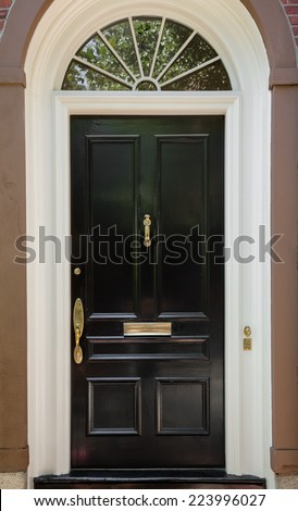 Closeup of Black Front Door with White Door Frame and Archway Window  - stock photo