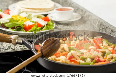 Closeup of black pan cooking vegetables and chicken for a mexican food in the kitchen - stock photo