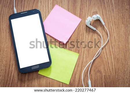 Closeup of black smartphone with white screen with headphones, sticky notes on wooden surface. Square image format. Instant photo split toning color effect - stock photo