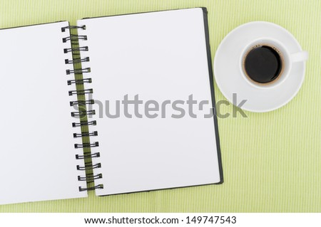 Closeup of Blank Diary and Cup of Coffee on Table - stock photo