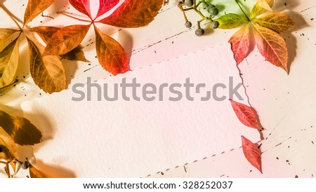 Closeup of blank letter surrounded by autumn leaves - stock photo
