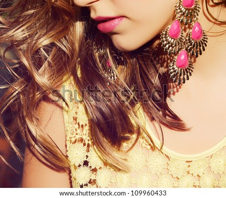 closeup of blond woman with long wet curly hair wearing pink lipstick and gold and pink neon earrings - stock photo