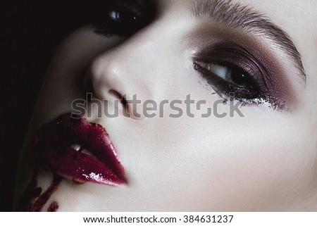Closeup of bloody red lips young girl. Dark fashion beautiful brunette woman. Glamour sensual posing - stock photo