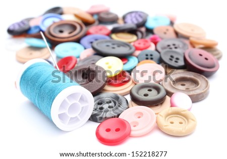 Closeup of blue thread with needle and collection of various sewing buttons. Isolated on white - stock photo