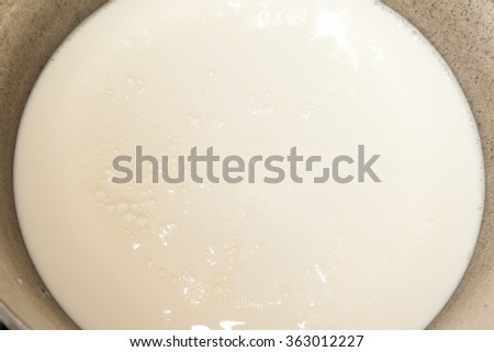 Closeup of boiling milk in kettle with selective focus - stock photo