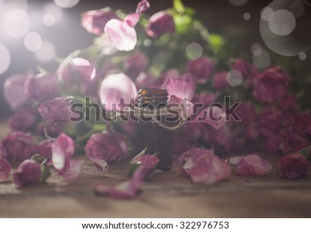 Closeup of bottle with rose essential oil with falling leaves on wooden background. With special bokeh lighting effect. - stock photo