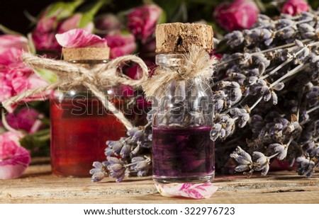 Closeup of bottles with rose and lavender essential oil on wooden background. - stock photo