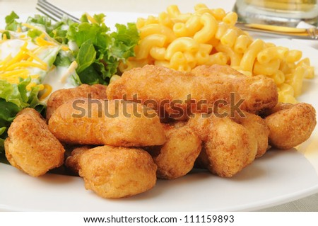 Closeup of breaded chicken strips with macaroni and cheese and salad - stock photo