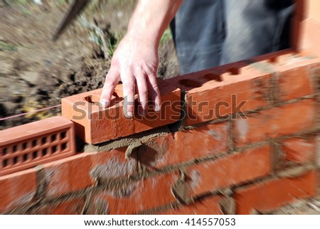 Closeup of bricklayer during the building of a house extension. Zoom effect applied centered on hand holding brick. - stock photo