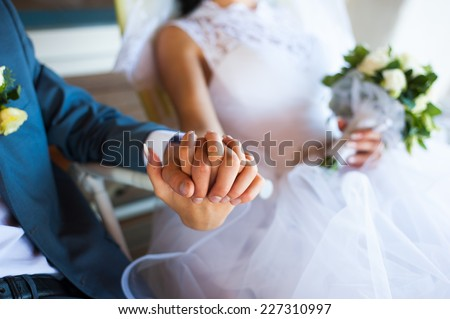 Closeup of bride and groom holding hands firmly together while sitting - stock photo