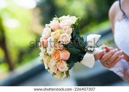Closeup of bride's hand holding a wedding bouquet - stock photo