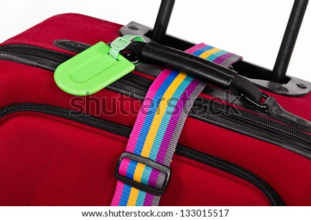 Closeup of bright green luggage tag and colorful belt on red suitcase - stock photo