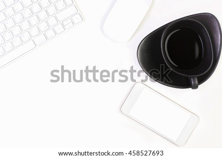 Closeup of bright white office desktop with computer mouse, keyboard, coffee cup and blank smartphone. Mock up - stock photo