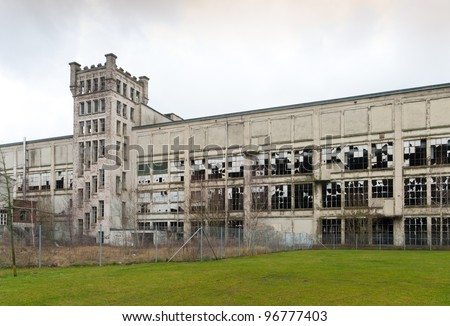 closeup of broken windows of an old factory ruin - stock photo