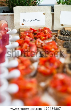 Closeup of bruschetta appetizers with tomato topping presented in rows and label with bruschetta text - stock photo