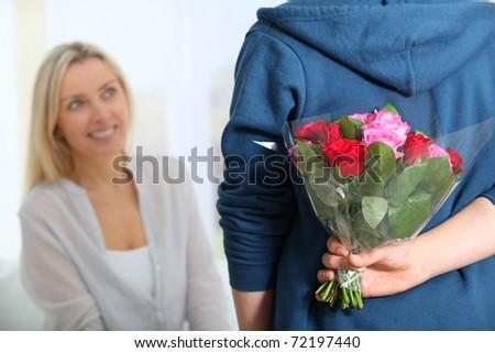 Closeup of bunch flowers hidden behind boy's back - stock photo