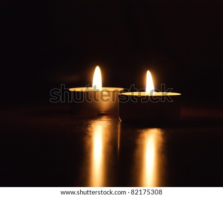 Closeup of burning candles isolated in front of black background - stock photo