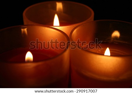 Closeup of burning red candles on a black background - stock photo