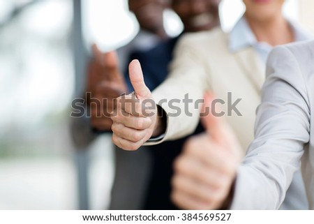 closeup of business people giving thumbs up - stock photo