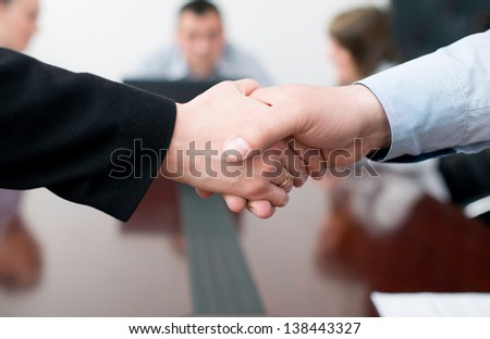 Closeup of business people shaking hands over a deal at office. - stock photo