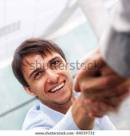 Closeup of business people shaking hands over a deal at office - Indoors - stock photo