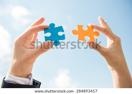 Closeup of business people wanting to put two pieces of puzzle together. Sky background. - stock photo