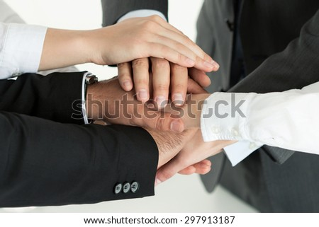 Closeup of business team showing unity with putting their hands together on top of each other. Concept of teamwork. - stock photo
