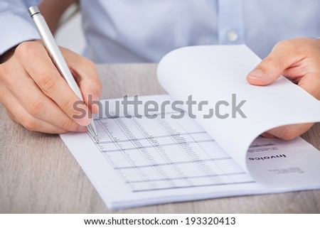 Closeup of businessman calculating accounts at desk - stock photo